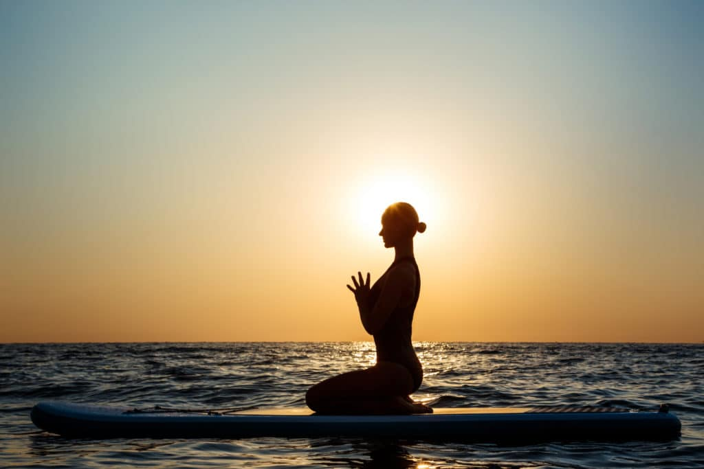 Silhouette Of Beautiful Woman Practicing Yoga On Surfboard At Sunrise