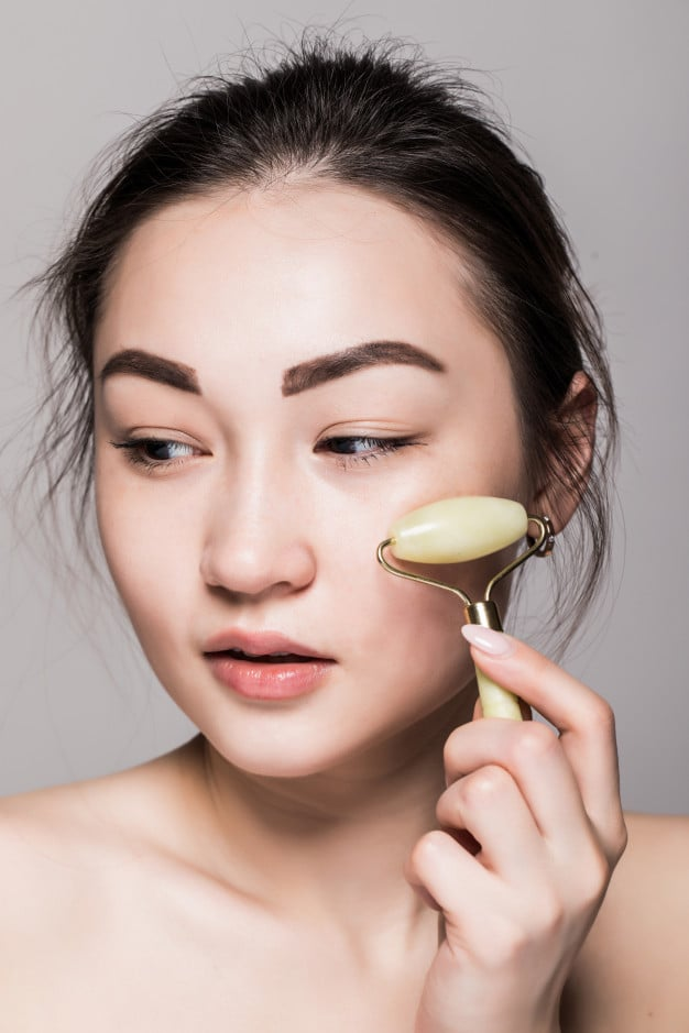 hermosa joven asiatica rodillo cara jade su piel perfecta primer plano cara belleza conceptual tratamientos faciales piedras semipreciosas aislado gris espacio copia 231208 1676
