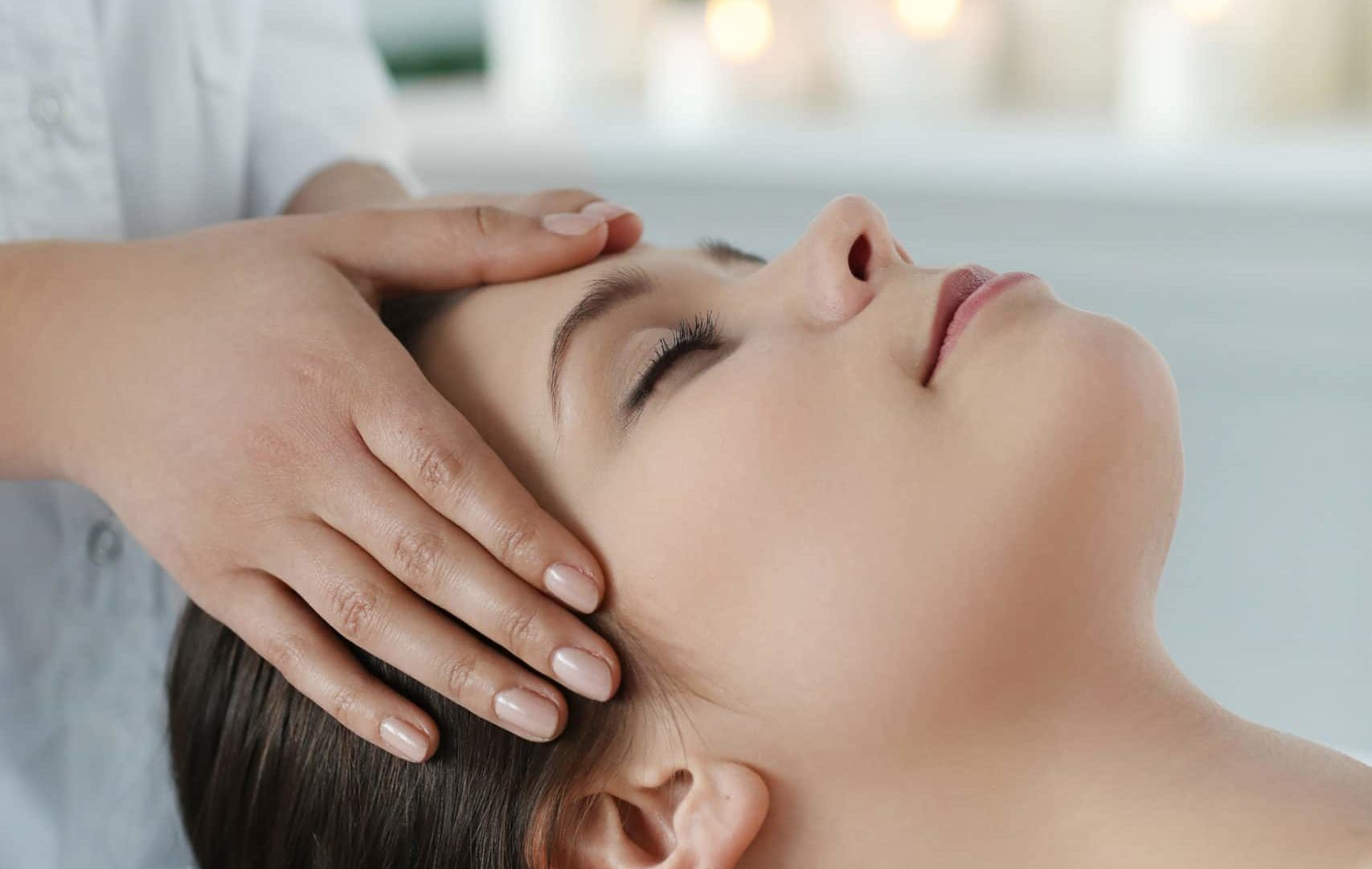 lying woman receiving massage craneosacral therapy 1 scaled e1618212121879