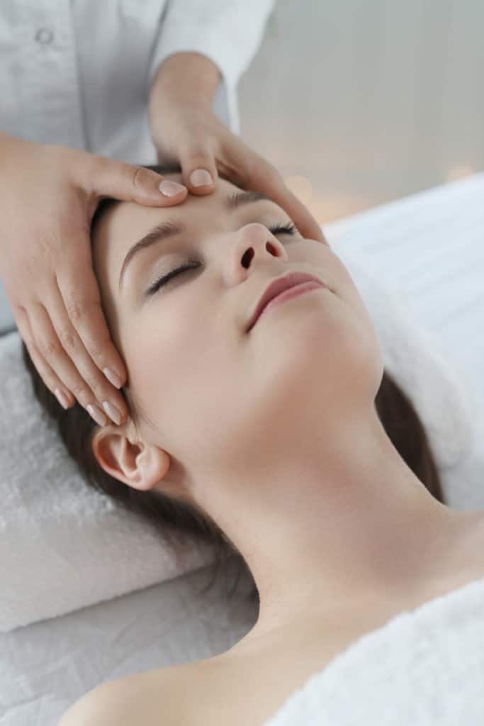 lying woman receiving massage craneosacral therapy