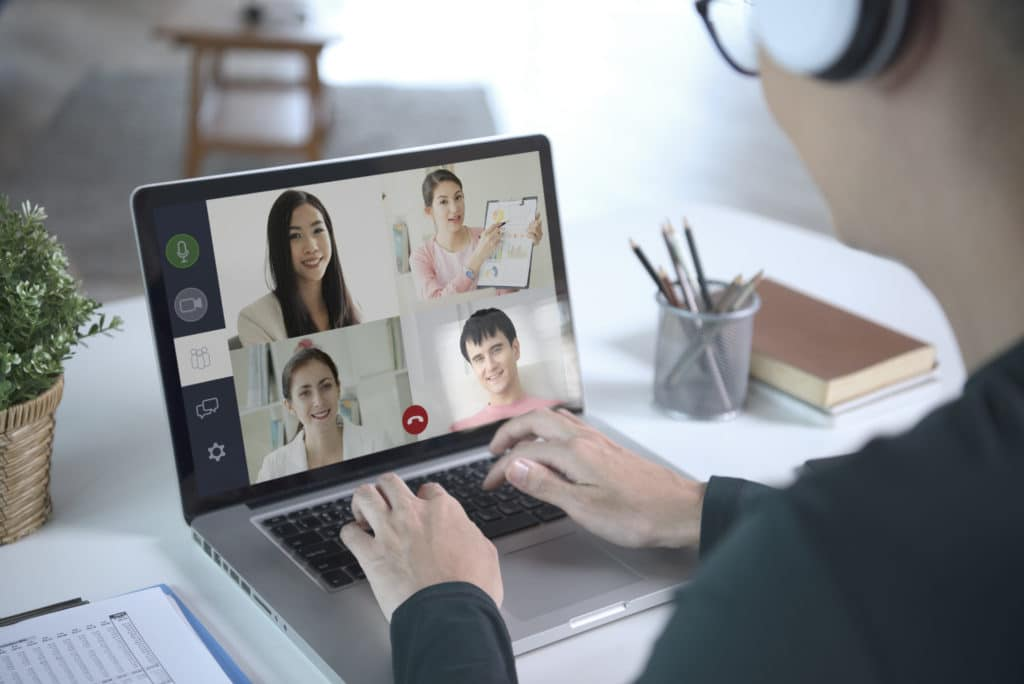 young asian businessman wear headphones working remotely from home and virtual video conference meeting with colleagues business people social distancing at home office concept