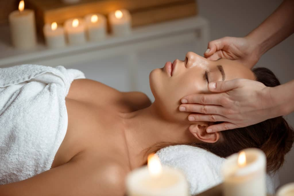 young woman having face massage relaxing in spa salon